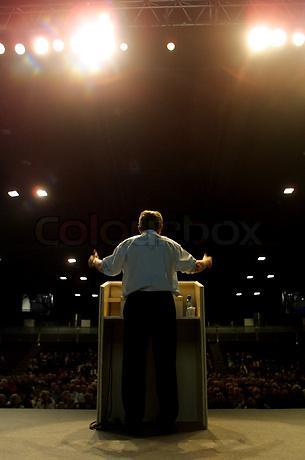 539617-543737-rear-view-of-man-giving-speech-from-stage-to-people